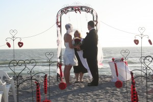 Wedding Arch With Red Accents On The Beach